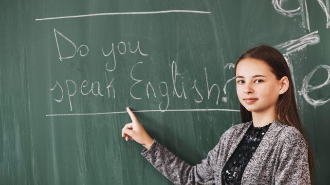 dziewczyna pokazuje palcem zdanie po angielsku na szkolnej tablicy