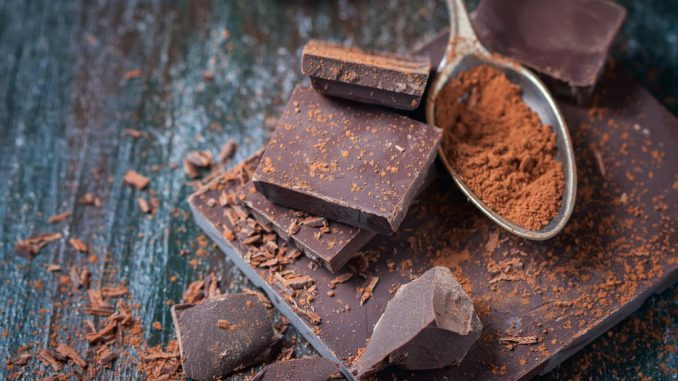 czekolada leży na stole obok łyżki pełnej kakao