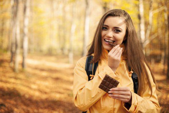 kobieta je czekoladę w trakcie spaceru po lesie