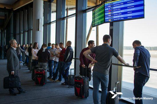 ludzie stoją z bagażami na lotnisku