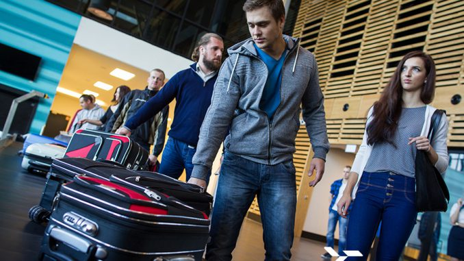 ludzie z bagażami przed odprawą bagażową