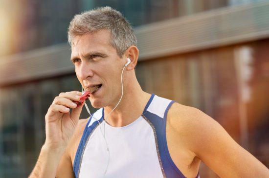 mężczyzna je czekolade w trakcie biegania