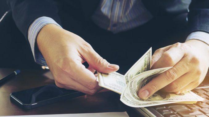 mężczyzna-w-garniturze-liczy-pieniądze-na-stole