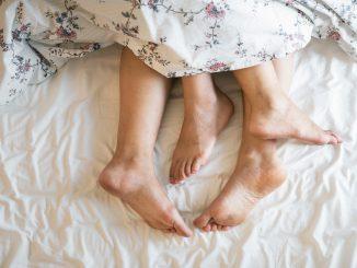 para leży w łóżku ze stopami wystającymi spod kołdry