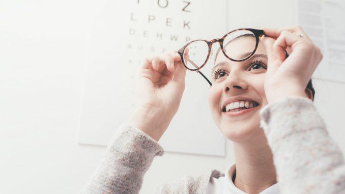 uśmiechnięta-kobieta-trzyma-w-rękach-okulary-i-patrzy-przez-nie-z-odległości.