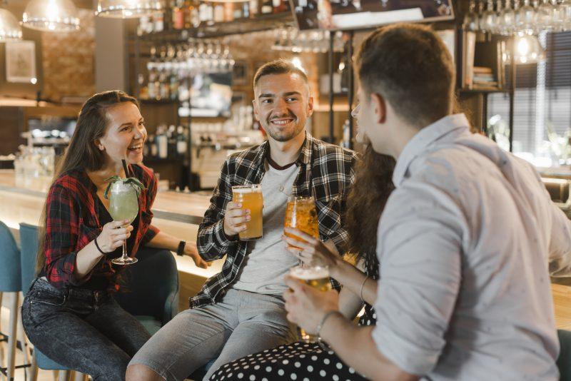 czwórka młodych ludzi siedzi w barze na hokerach