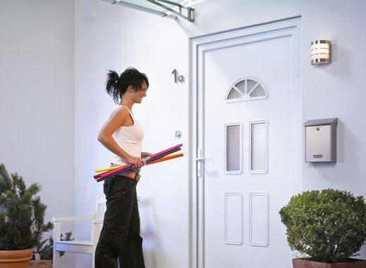 kobieta stoi przed drzwiami i niesie kolorowy papier w rolkach