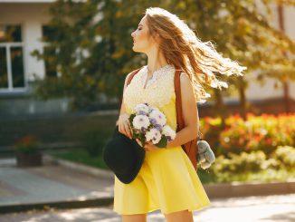 kobieta-w-żółtej-sukience-idzie-ulicą-i-trzyma-białe-kwiaty-w-rękach