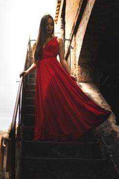 kobieta w czerwonej sukni schodzi po schodach