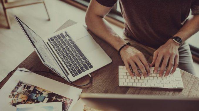 mężczyzna-siedzi-przy-biurku-i-pisze-na-klawiaturze-laptopa