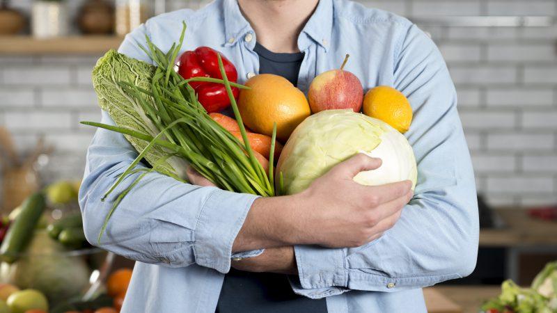 mężczyzna trzeba w rękach owoce i warzywa