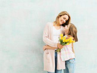 matka stoi z córką z kwiatami na dzień matki