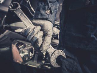mechanik-stoi-przed-samochodem-z-kluczem-francuskim-w-dłoni