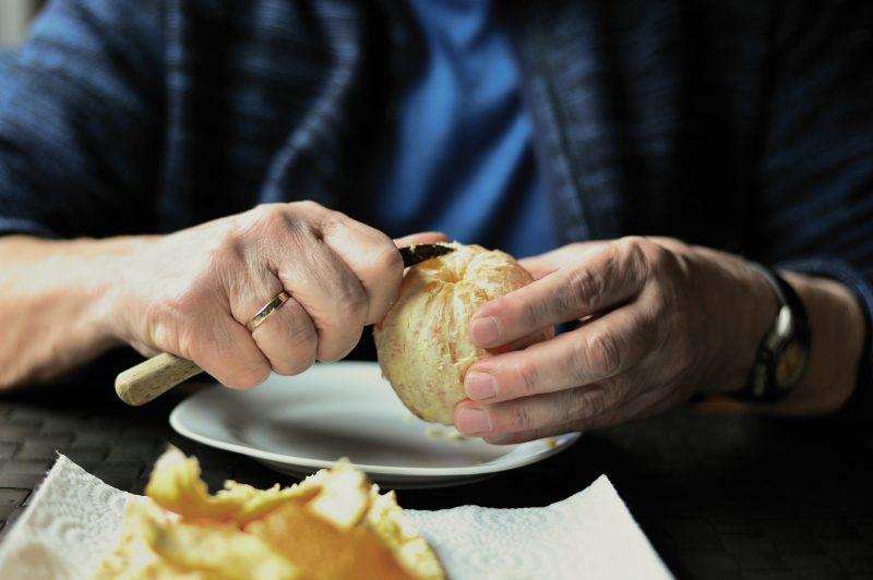 starszy człowiek obiera mandarynkę siedząc przy stole