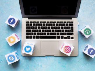 zbliżenie na klawiature laptopa z rozrzuconymi sześcianami z logami social media