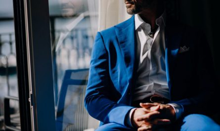 elegancki mężczyzna w garniturze pozuje do zdjęcia i patrzy za okno