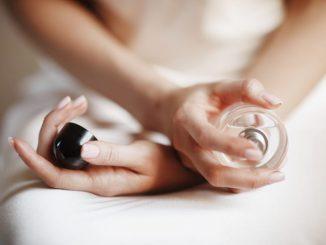 kobieta-siedzi-na-łóżku-ze-skrzyżowanymi-rękami-w-których-trzyma-perfumy