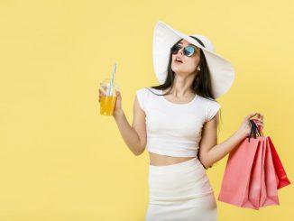 kobieta-w-białym-kapeluszu-trzyma-drinka-i-torby-z-zakupami