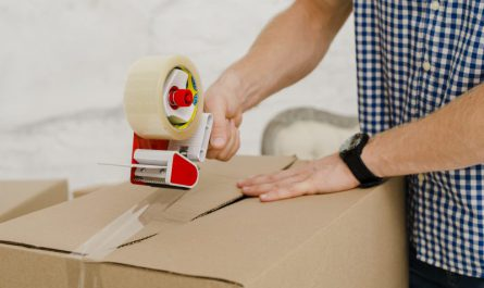 mężczyzna-zamyka-kartonowe-opakowanie-za-pomocą-taśmy-klejącej