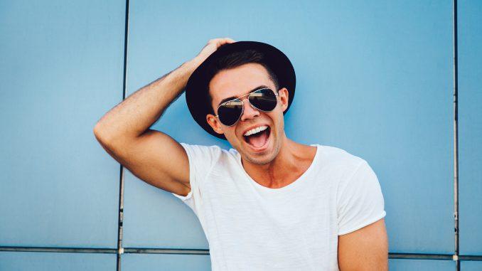 muskularny-mężczyzna-w-kapeluszu-i-białej-koszulce-uśmiecha-się-do-zdjęcia