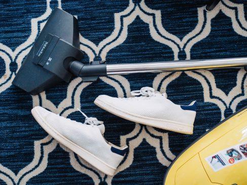 robot sprzątający leży obok butów na podłodze w domu