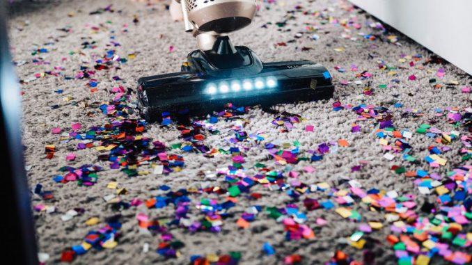 robot sprzątający oczyszcza dywan z resztek konfetti