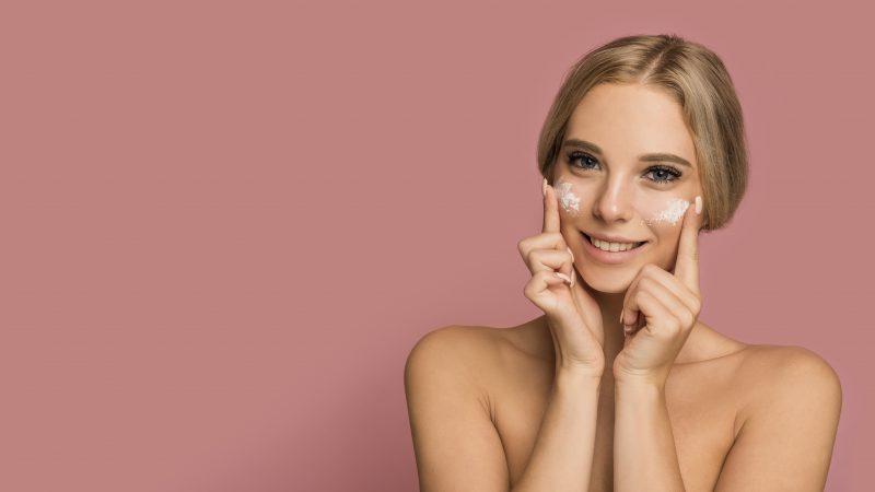 uśmiechnięta-kobieta-używa-kremu-do-twarzy