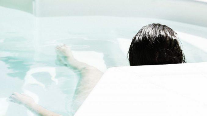 zdjęcia kobiety leżącej w wannie z hydromasażem