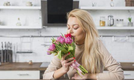 blond kobieta wącha bukiet róż i siedzi w kuchni