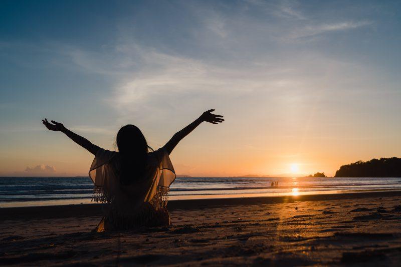 kobiet-siedzi-na-plaży-i-wyciąga-ręce-w-kierunku-słońca