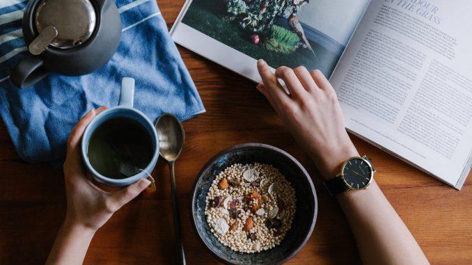 kobieta je śniadanie i czyta modny magazyn