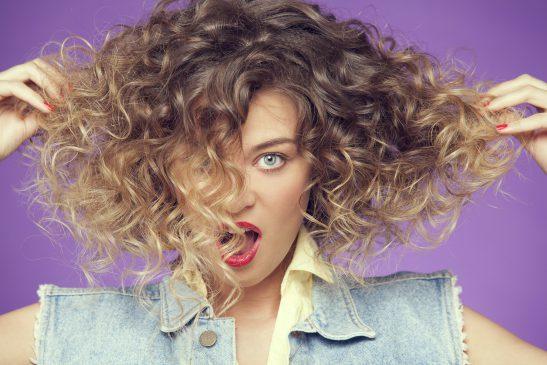 kobieta-z-kręconymi-włosami-pozuje-do-zdjęcia
