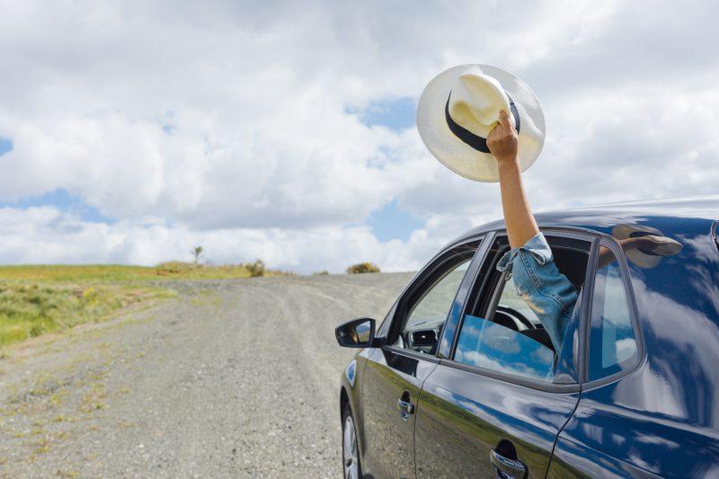mężczyzna-trzyma-w-ręku-kapelusz-i-wystawia-go-za-okno-samochodu-w-geście-pożegnania