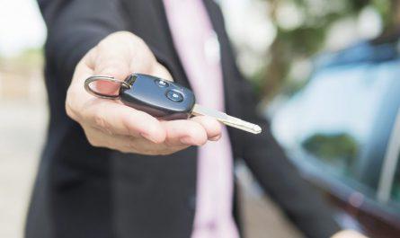 mężczyzna-wręcza-klucze-do-samochodu-w-salonie