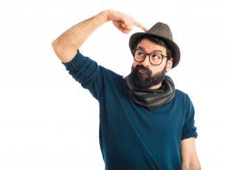 mężczyzna-z-brodą-w-kapeluszu-i-szaliku-drapie-się-po-głowie-w-geście-zastanawiania