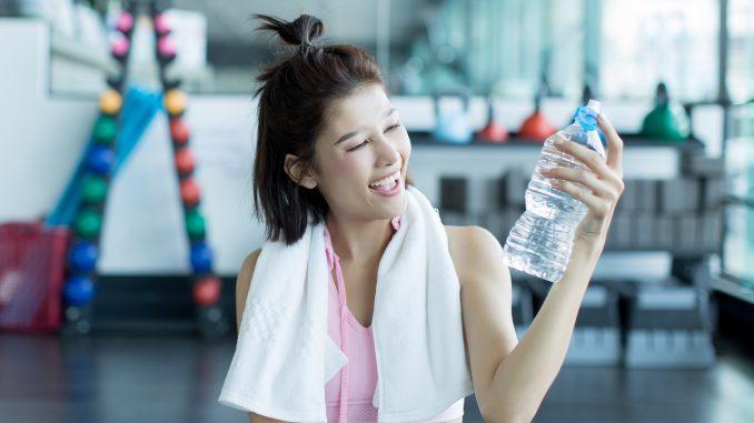 uśmiechnięta-kobieta-trzyma-butelkę-wody-po-treningu