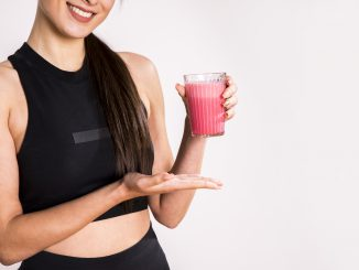 uśmiechnięta kobieta trzyma zdrowy szejk w szklance
