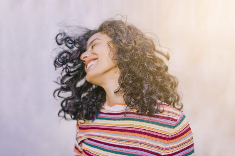 uśmiechnięta-kobieta-z-kręconymi-włosami-macha-głową-na-słońcu