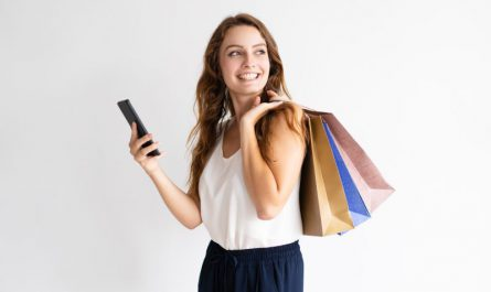 uśmiechnięta-kobieta-z-telefonem-komórkowym-i-zakupami