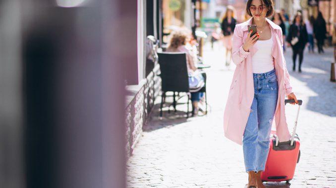 kobieta-z-walką-idzie-ulicą-i-patrzy-w-smartfona