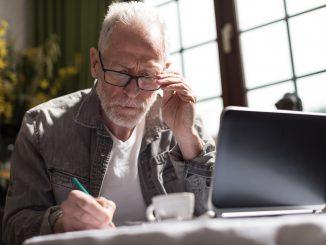 starszy-mężczyzna-wypełnia-dokument-w-skupieniu