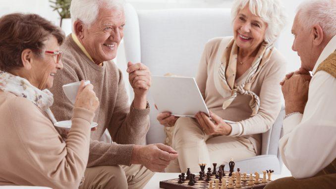 grupa starszych osób siedzi w salonie i gra w szachy