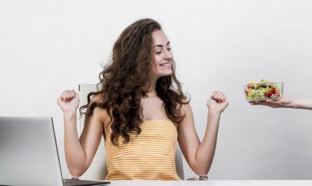 kobieta je sałatke przy komputerze