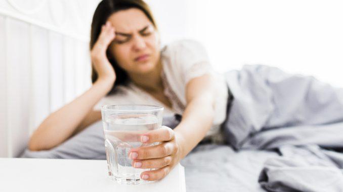 kobieta leży na kacu w łóżku i trzyma szklanke wody