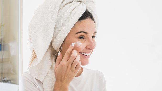 kobieta nakłada sobie żel na twarz przy lustrze w łazience