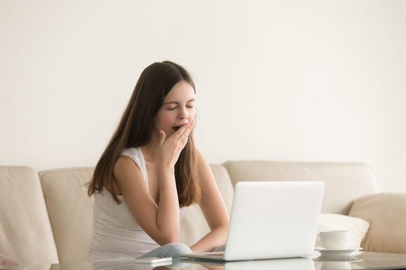 kobieta-ziewa-siedzi-na-kanapie-przy-laptopie.