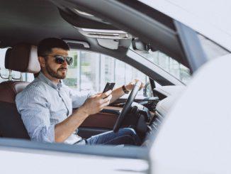 biznesmen w samochodzie pisze na telefonie