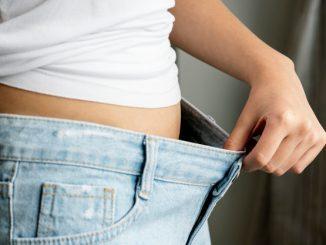 kobieta pokazuje ile schudła na za dużych spodniach