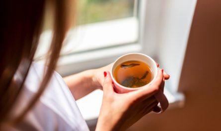 kobieta trzyma kubek czerwonej herbaty