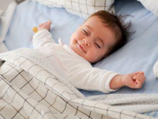 uśmiechnięte dziecko leży w łóżku i śpi